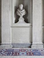 Moderne Fliesen mit geometrischen Mustern vor antiker Büste zwischen Säulen