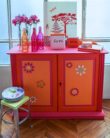 Cabinet decoratively painted in red, orange and hot pink