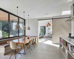 Dining table with shell chairs and corner bench in modern kitchen-dining room
