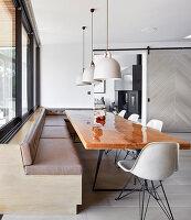 Lackierter Holztisch mit Schalenstühlen und Eckbank