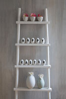 Easter arrangement of white eggs decorated with lettering reading 'Happy Easter' on ladder shelves