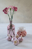 Garlic bulbs, pickled garlic and vase of carnations