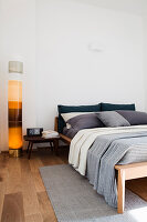 Decorative water column lamp next to wooden bed in bedroom