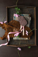 Chocolate lollies, books and asters on antique wooden tray