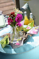 Paper boats and garden flowers as decoration for picnic on lake