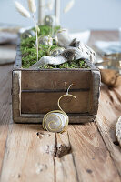 Handmade table centrepiece with snails made from pebbles and wire
