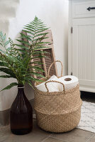Fern leaves in large brown bottle and basket of toilet rolls in bathroom