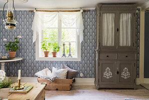 Restaurierter Vitrinenschrank neben Holzkiste mit Kissen im Wohnzimmer mit gemusterter Tapete