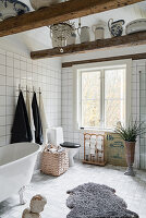 Free-standing bathtub in large bathroom decorated in vintage style