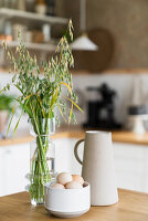 Fresh eggs in bowl, vase of grasses and jug on wooden table
