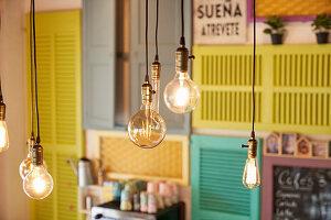 Hängende Glühbirnen vor einer Wand mit bunten Fensterläden