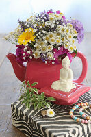 Summer bouquet in teapot next to Buddha figurine on teapot lid