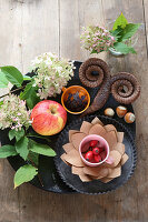 Autumnal table decoration of apples, rose hips, hydrangeas and pine cone curled into horns