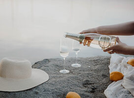 Woman pouring glasses of sparkling wine on rocks on lake shore
