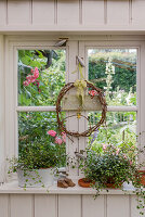 Wreath and plants in window with view of summer garden