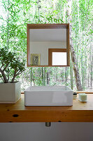 Washstand and square mirror in front of large window with view of green plants outside
