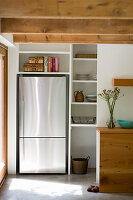 Modern stainless steel fridge in niche next to kitchen shelves