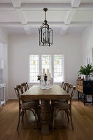 Solid wooden dining table in elegant, white interior with coffered ceiling