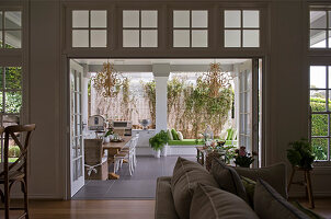 View through open double doors onto roofed terrace furnished with dining table and bench between pillars