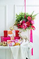 Wandkranz mit Rosenblüten davor verpackte Weihnachtsgeschenke