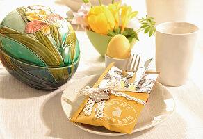 DIY-Besteckhalter mit Stempelmotiv und Keramik-Osterei auf Frühstückstisch