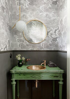 Green washstand with copper sink in guest toilet with grey walls