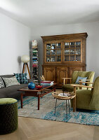 Antique glass-fronted cabinet, vertical book shelf and upholstered seating in living room