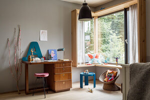 Desk and stool in child's bedroom in child's bedroom with grey wall