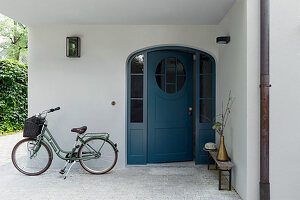 Bicycle and half-opened front door in entrance area