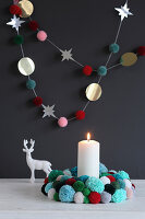 Christmas wreath and garland of pompoms against black wall