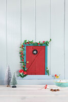Handmade gnome-sized door on wall as Christmas decoration