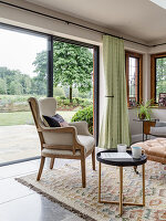 Armchair and round side table next to terrace windows in living room