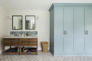 Twin sinks on washstand and grey cupboard in bathroom