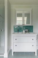 Washstand below mirrored wall cabinet in bathroom