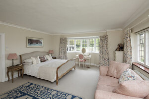 Double bed, sofa and dressing table in bright bedroom with bay window