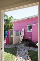 Pink house with outdoor shower and surfboard in garden