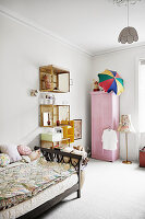 Bed, shelves made from old crates and pink wardrobe in girl's bedroom