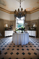 Antique chests of drawers, round table and chandelier in stylish foyer