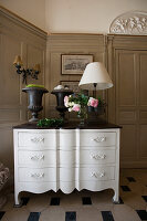 Urns, table lamps and vase of roses on white, antique chest of drawers