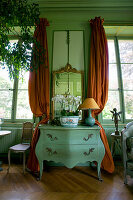 Antique chest of drawers between windows with curtains in green French parlour