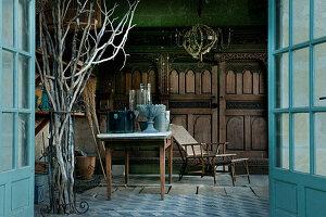 View through open double doors into summerhouse with antique gardening equipment