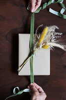 Hands tying velvet ribbon around posy of dried grasses