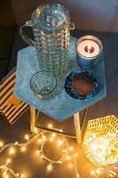 Glass jug and candle on side table with festive fairy lights below