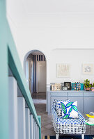 View past staircase to blue-and-white, polka-dot, loose-covered armchair and pale grey sideboard
