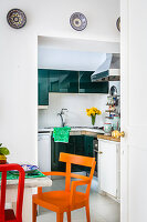 Dining table and colourful chairs next to open doorway leading into kitchen
