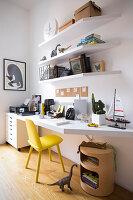 Weiße Schreibtischplatte, darüber weiße Regale und gelber Stuhl im Jugendzimmer
