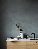 Aufgeschlagenes Buch auf minimalistischer Küchenzeile vor grauer Wand