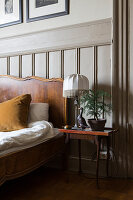 Bedside table in bedroom with classic wainscoting