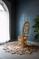 Peacock chair on sisal rug against dark blue wall and next to large arched window