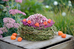 Wreath of hop vines with hydrangea blossoms, lanterns, and Pink bell heather